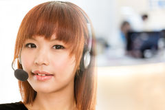 Asian woman with headset microphone fades into call center. Asian female wearing a headset with microphone fasing into defocused office or call center in Stock Photos