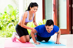 Asian woman helping man with push-up royalty free stock images