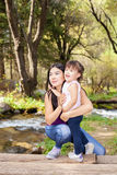 Asian Woman with her little daughter in the woods near the river standing on a log Stock Photos