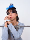 Asian woman with her wrists restrained with chain. Pretty Asian woman with her wrists restrained with chain wears mini blue hat hair clip Royalty Free Stock Photography