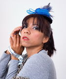 Asian woman with her wrists restrained with clamp. Pretty Asian woman with her wrists restrained with metal clamp wears mini blue hat hair clip Stock Photos