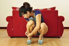 Asian woman, high heel shoes, red sofa royalty free stock photos