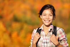 Asian woman hiker hiking in Autumn forest. Hiker hiking in Autumn forest. Young outdoors woman smiling happy during hike in beautiful fall colored forest. Fresh Royalty Free Stock Photos