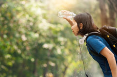 Asian woman hiker pouring water from bottle on her face with nat Royalty Free Stock Photos