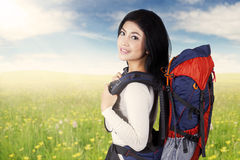 Asian woman with hiking bag on meadow Stock Image
