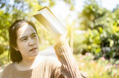 Asian woman hold a book covering the sun to prevent facial skin damage, against sunlight,UV rays problem to make melasma and