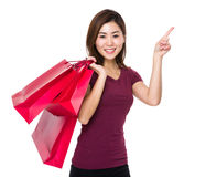 Asian woman hold with shopping bag and finger point up Royalty Free Stock Image
