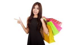 Asian woman hold shopping bags point to empty space Stock Image