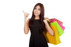 Asian woman hold shopping bags point up and look at camera Stock Images