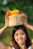 Asian woman holding a basket of bell peppers and mango Royalty Free Stock Image