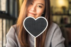Asian woman holding a blank heart shape blackboard sign with feeling happy and in love Royalty Free Stock Photos