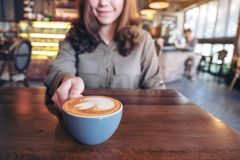 An asian woman holding a blue cup of hot latte coffee with latte art on wooden table stock photo