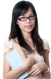 Asian woman holding a book. A young asian female holding a blue book while wearing glasses Stock Photography