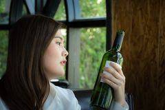 Asian woman holding a bottle of wine/Woman selecting a bottle of wine. In restaurant Royalty Free Stock Photo