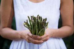 Asian woman holding a bunch of asparagus Royalty Free Stock Photography