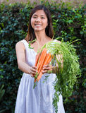 Asian woman holding a bunch of carrots Stock Photo