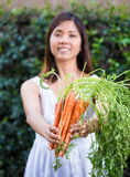 Asian woman holding a bunch of carrots Stock Photos