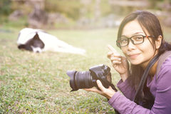 Asian woman holding camera and pointing to the dog. Taking photograph Stock Photography