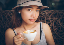 Asian woman holding a coffee cup. In hand and see camera. Vintage retro style photo with color filters, vignette effect, and some fine film noise added Royalty Free Stock Images