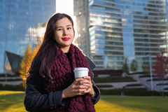 Asian woman holding coffee in hand, standing outdoors behind skyscrapers Royalty Free Stock Photo
