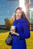 Asian woman holding coffee in hand, standing outdoors behind skyscrapers Stock Photo