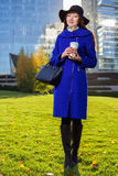 Asian woman holding coffee in hand, standing outdoors behind skyscrapers Stock Images