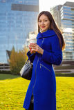 Asian woman holding coffee in hand, standing outdoors behind skyscrapers Royalty Free Stock Photos