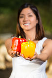 Asian woman holding a colorful bell peppers Stock Image