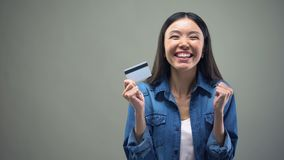 Asian woman holding credit card in hands, cash back services, grey background. Stock footage stock video footage