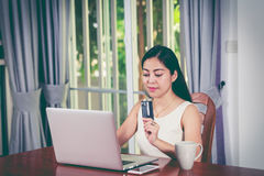 Asian woman holding credit card. Online shopping concept. Cross. Beautiful asian woman holding credit card and making order at home. Young adult using laptop Stock Photography