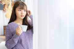 Asian woman holding a cup of coffee in her hands on the light ba stock images