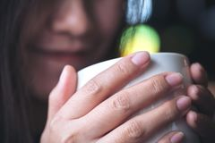 Asian woman holding and drinking hot coffee with feeling good and smiley face Stock Photos