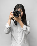 Asian woman holding DSLR camera. Royalty Free Stock Images