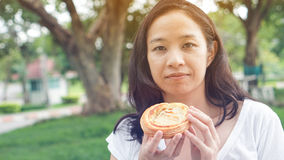 Asian woman holding and eating fresh baked bakery in green backg Stock Photos