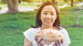 Asian woman holding and eating fresh baked bakery in green backg Royalty Free Stock Photo