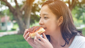 Asian woman holding and eating fresh baked bakery in green backg Stock Image