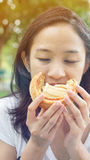 Asian woman holding and eating fresh baked bakery in green backg Royalty Free Stock Photos