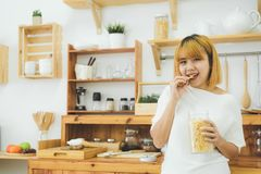 Asian woman holding and eating junk food snack and chips in her kitchen at home. Asian woman holding and eating junk food snack and chips in her kitchen at home stock photos