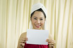 Asian woman holding empty blank banner and acting. she wear a skirt to cover her breast after wash hair, Wrapped in Towels After royalty free stock photo