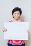 Asian woman holding empty white picture frame in studio shot, sp Royalty Free Stock Photography