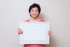 Asian woman holding empty white picture frame in studio shot, sp Stock Photos