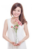 Asian woman holding flowers in a vase Royalty Free Stock Photo