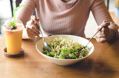 Asian woman holding fork and spoon to eating vegetable salad wit. Attractive asian woman holding fork and spoon to eating vegetable salad with orange juice Stock Photos