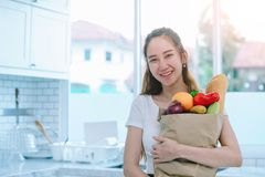 Asian woman holding the fruits. In paper bag in her kitchen at her sweet home to making the dinner Royalty Free Stock Images
