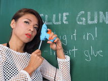 Asian woman holding a glue gun stock photography