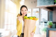 Asian woman holding groceries bag and credit card in market Stock Photos