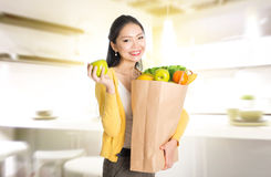 Asian woman holding groceries bag in kitchen Stock Photo