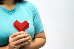 An asian woman holding heart origami in front of her chest. A woman giving red heart paper to someone. Love and give concept for v. Alentine day Stock Photography