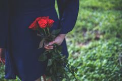 An Asian woman holding and hiding red roses bouquet on her back with green nature Royalty Free Stock Images