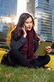 Asian woman holding iPad in hand, sitting instanding outdoors behind skyscrapers Royalty Free Stock Images